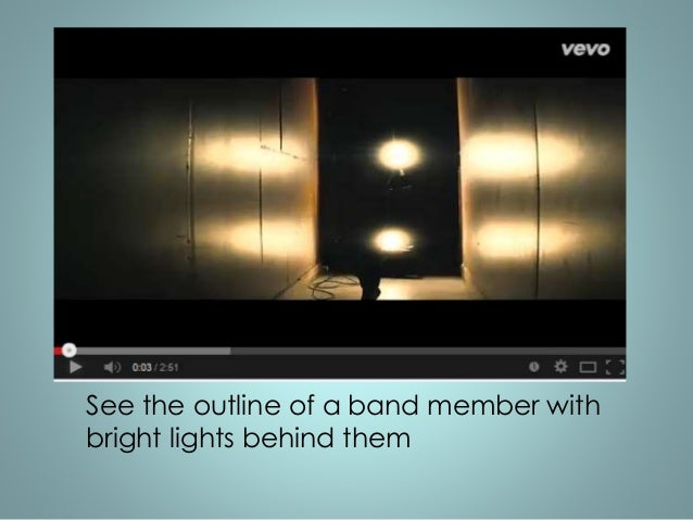 See the outline of a band member with  bright lights behind them