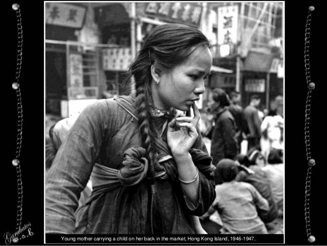 Young mother carrying a child on her back in the market, Hong Kong Island, 1946-1947.