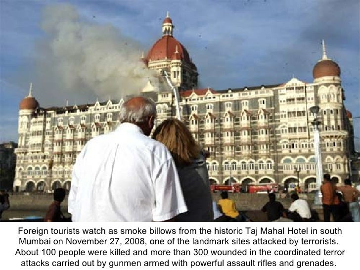 Foreign tourists watch as smoke billows from the historic Taj Mahal Hotel in south Mumbai on November 27, 2008, one of the...