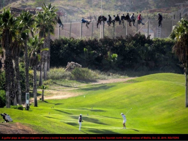 A golfer plays as African migrants sit atop a border fence during an attempt to cross into the Spanish north African encla...