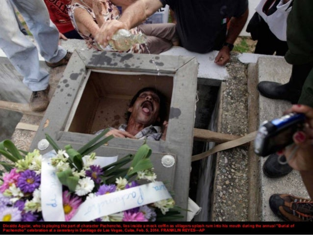 Divaldo Aguiar, who is playing the part of character Pachencho, lies inside a mock coffin as villagers splash rum into his...