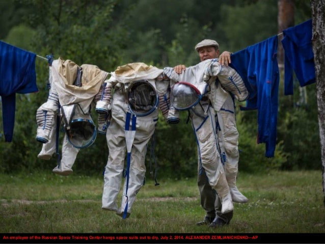 An employee of the Russian Space Training Center hangs space suits out to dry, July 2, 2014. ALEXANDER ZEMLIANICHENKO—AP