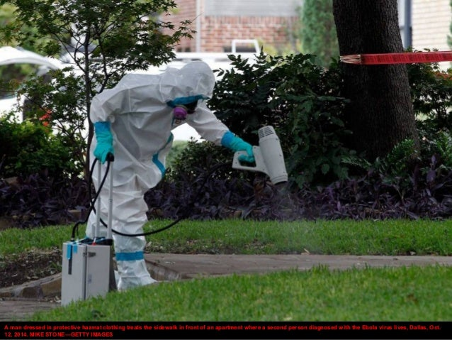 A man dressed in protective hazmat clothing treats the sidewalk in front of an apartment where a second person diagnosed w...