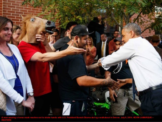 A man wearing a horse mask reaches out to shake hands with U.S. President Barack Obama during a walkabout in Denver, July ...