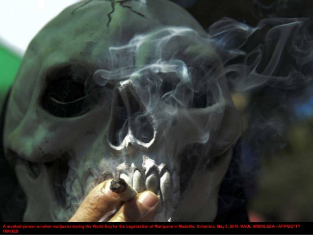 A masked person smokes marijuana during the World Day for the Legalization of Marijuana in Medellin, Colombia, May 3, 2014...