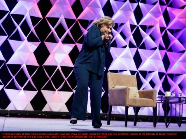 Former Secretary of State Hillary Clinton ducks after a woman threw an object toward her while she was delivering remarks ...