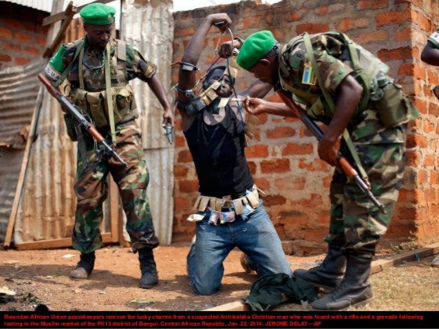 Rwandan African Union peacekeepers remove the lucky charms from a suspected Anti-balaka Christian man who was found with a...