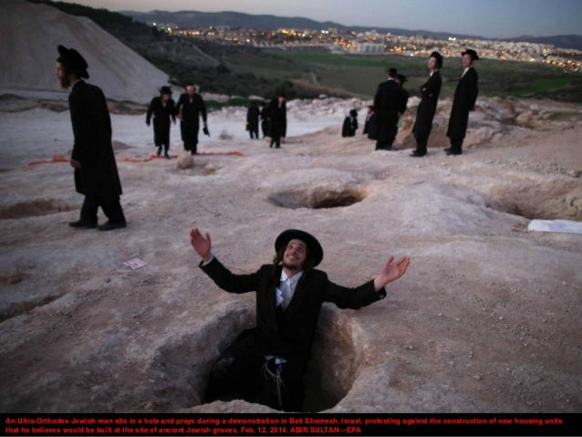 An Ultra-Orthodox Jewish man sits in a hole and prays during a demonstration in Beit Shemesh, Israel, protesting against t...