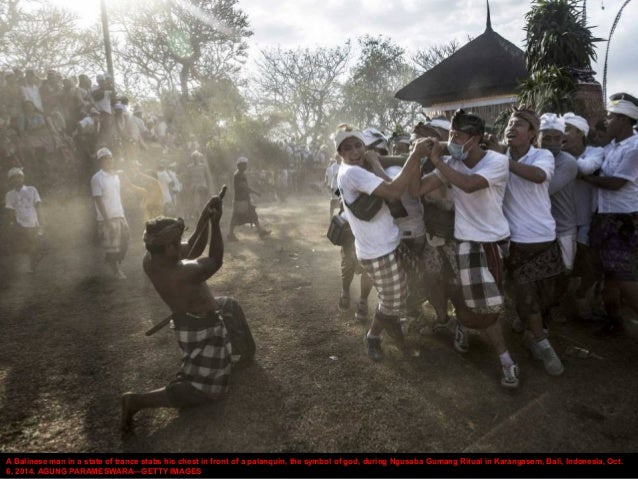 A Balinese man in a state of trance stabs his chest in front of a palanquin, the symbol of god, during Ngusaba Gumang Ritu...