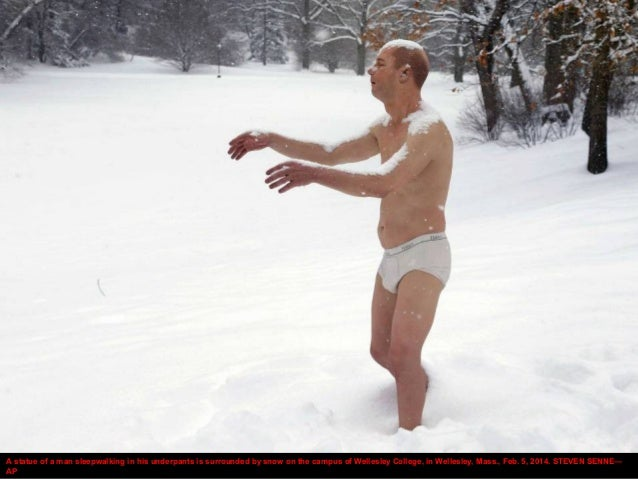 A statue of a man sleepwalking in his underpants is surrounded by snow on the campus of Wellesley College, in Wellesley, M...