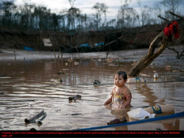 Prisaida, 2, sits in the shallow waters of a polluted lagoon as her parents mine for gold nearby in La Pampa in Peru's Mad...