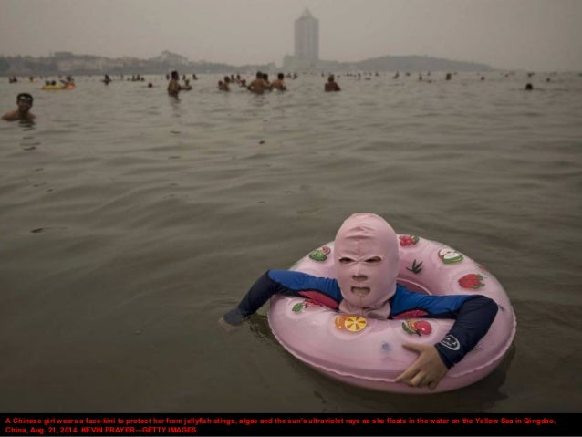 A Chinese girl wears a face-kini to protect her from jellyfish stings, algae and the sun's ultraviolet rays as she floats ...