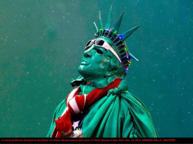 A street performer dressed as the Statue of Liberty stands among light snow in Times Square in New York, Dec. 10, 2014. AN...