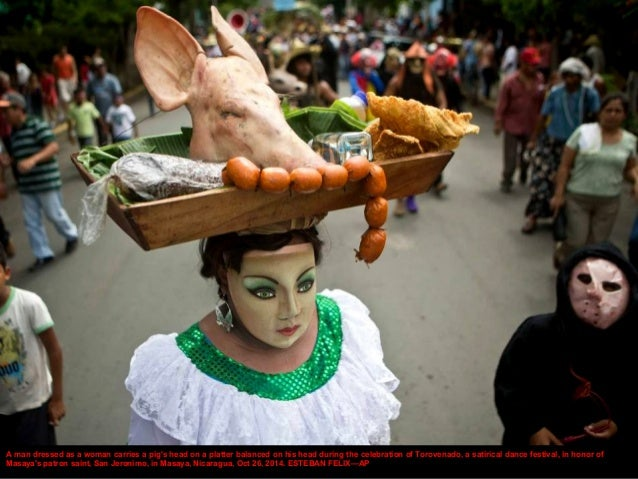 A man dressed as a woman carries a pig's head on a platter balanced on his head during the celebration of Torovenado, a sa...