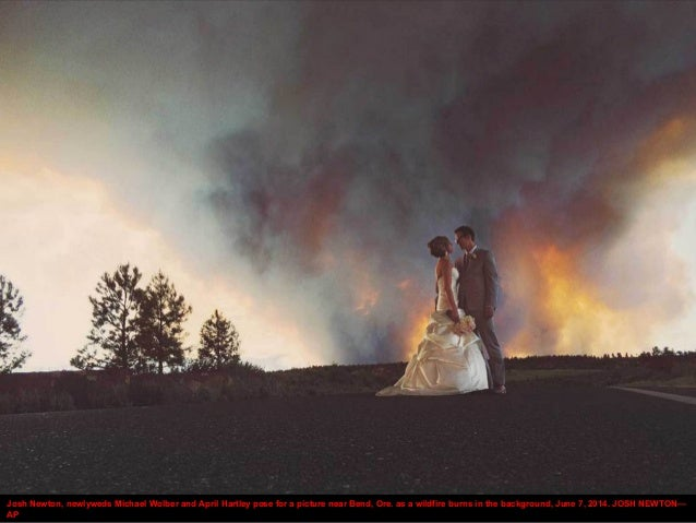 Josh Newton, newlyweds Michael Wolber and April Hartley pose for a picture near Bend, Ore. as a wildfire burns in the back...
