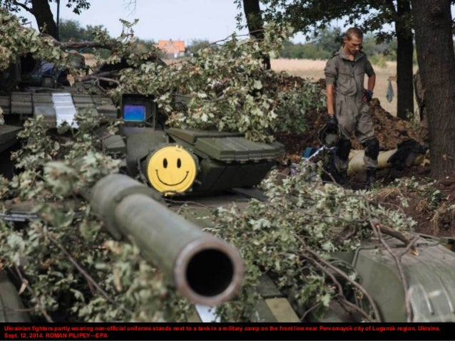 Ukrainian fighters partly wearing non-official uniforms stands next to a tank in a military camp on the front line near Pe...