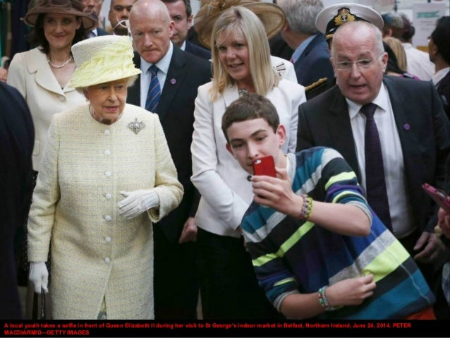 A local youth takes a selfie in front of Queen Elizabeth II during her visit to St George's indoor market in Belfast, Nort...