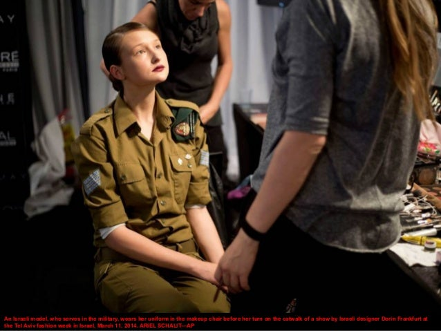 An Israeli model, who serves in the military, wears her uniform in the makeup chair before her turn on the catwalk of a sh...