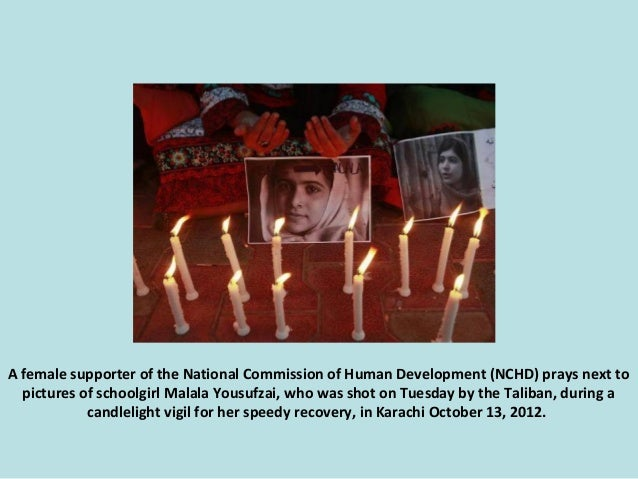 A female supporter of the National Commission of Human Development (NCHD) prays next to pictures of schoolgirl Malala Yous...