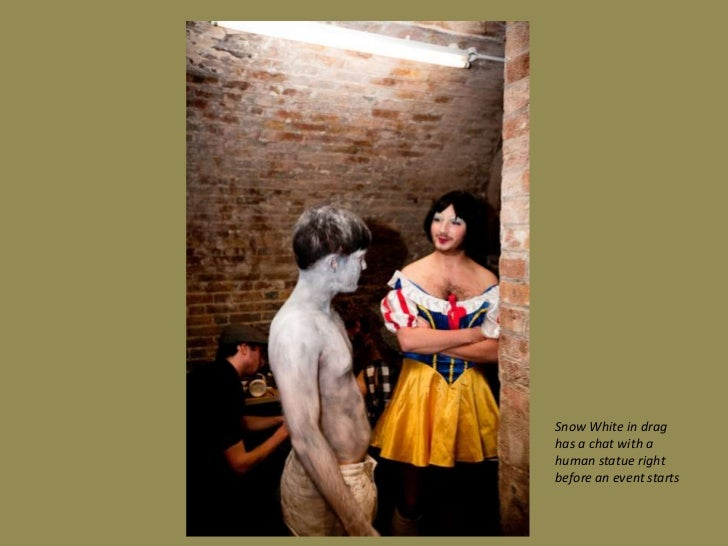 Snow White in drag has a chat with a human statue right before an event starts<br />